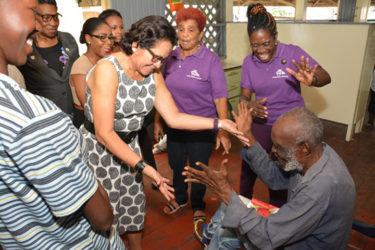 Lewis  Hart, a resident of The Palms Geriatric Home charmed First Lady,  Sandra Granger  when she visited the facility to host a special 'spa' exercise for the male residents. (Ministry of the Presidency photo)