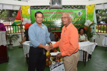 Land Information and Mapping Manager, Naseem Nasir (left) presenting a special award to Mr. Abdul Khan who will be proceeding into retirement after serving the Commission for 15 years. (Ministry of the Presidency photo)