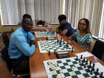 Sheriffa Ali (right) smiles as she opposes Frankie Farley during their game at the Andrew Arts Memorial Chess Tournament last Sunday at the National Resource Centre. Ali is a member of the 2016 Olympiad chess team which represents Guyana in Azerbaijan in September. She has been playing competitively for the past decade, and should do well at the Olympiad. On her right is her brother Saeed Ali. (Photo by Ryan Singh)
