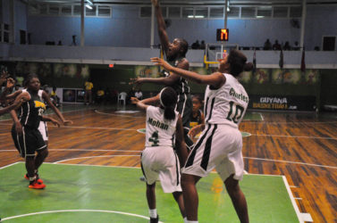 Shauliqua Fahie (centre) of BVI in the process of scoring a jump shot while being challenged by several Guyanese players during their matchup in the CBC Girls u16 Championship at the Cliff Anderson Sports Hall.