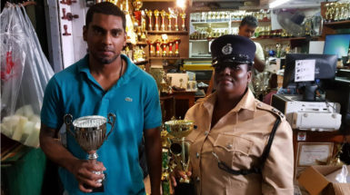 Jonathan Sunich, Canada-born son of Ramesh Sunich CEO of the Trophy Stall and Inspector Cynthia Kelly, Chairperson of the Guyana Association of Police Women display the champion trophies for Sunday's Rising Sun Turf Club meet on Sunday.