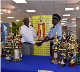 President of Courts' Sports Club, Ricardo Manbodh, hands over the trophies to Coach of the Police Sports Club, Linden Wilson.