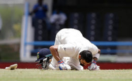 India captain Virat Kohli celebrates his maiden double century by kissing the turf at the Vivian Richards Cricket Ground. (Photo courtesy WICB)