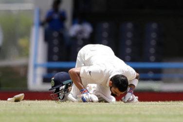 India captain Virat Kohli celebrates his maiden double century by kissing the turf at the Vivian Richards Cricket Ground. (Photo courtesy WICB)