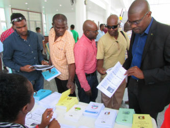 Minister of Public Infrastructure David Patterson and contractors checking out the Guyana Revenue Authority (GRA) booth at the procurement symposium for new entrant contractors, which was held at the Arthur Chung Convention Centre yesterday. (Minister of Public Infrastructure photo)