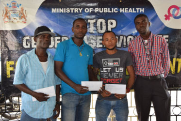 Petra Organization representative Mark Alleyne (right) poses with members from the competing teams of North East La Penitence (left), Broad Street (2ndleft) and Tucville (2ndright) following the conclusion of the presentation ceremony yesterday.