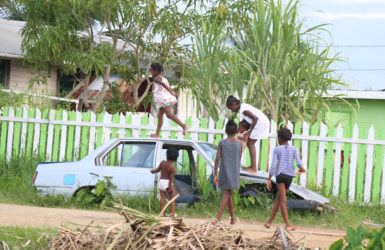 School's out and an abandoned car in 'C' Field Sophia served as a play area for these children yesterday. (Photo by Keno George)