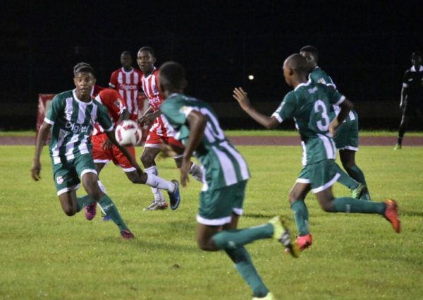Omar Brewley (left) of Wismar/Christianburg in the process of receiving a pass while being pursued by several players from Sir Leon Lessons during their semi-final fixture at the Leonora Sports Facility in the Digicel Schools Football Championship.