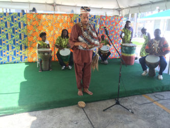 Bishop Andre Irving (centre) performing a libation and African prayer accompanied by drumming performed by the Buxton Fusion Group (background) during the Ministry of Education, Department of Culture, Youth and Sport's launching of Emancipation celebrations yesterday.  (Dhanash Ramroop photo)