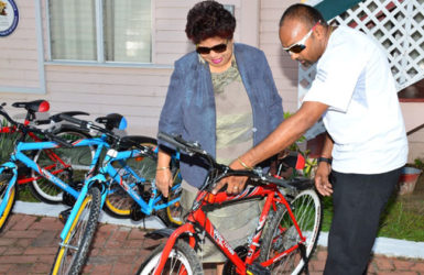 Deavindra Jagroo showing Minister of Social Cohesion, Amna Ally one of the bikes. (Ministry of the Presidency photo)