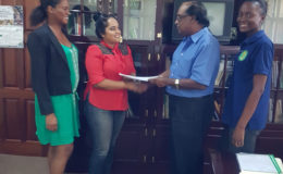 Chief Executive Officer of NAREI, Dr. Oudho Homenauth (second from right) presents a copy of the contract to the contractor S&K Construction Services. Also in the picture are head of the Mangroves Department Kene Moseley and NAREI's Engineer Luandra Jack. (Ministry of Agriculture photo)