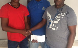 Juvenile cycle champion Zaman Khan's (left) sojourn to the Junior Caribbean Cycling Championships was made possible by Steven Edwards (right). Coach of the team Randolph Roberts is pictured at centre.