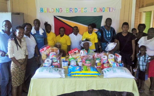 The elderly women (seated behind food items), pose with members of Building Bridges Foundation and others.