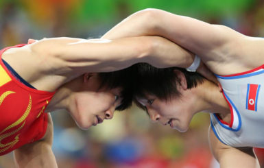 Zhong Xuechun of China and Jong Myong-Suk of North Korea compete in women's freestyle 53kg wrestling. REUTERS/Toru Hanai