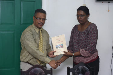 Chief Labour Officer Charles Ogle (left) hands over the report to Human Resources Manager of John Fernandes Limited Donna Roberts Benjamin