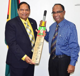 Prime Minister Moses Nagamootoo (left) collects an autographed Guyana Amazon Warriors bat from team Manager Omar Khan