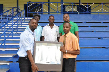 Director of Sport, Christopher Jones (left) hands over one of 15 floodlamps that will be erected at the MSC Ground to Regional Executive Officer, Region 10, Gavin Clarke yesterday.