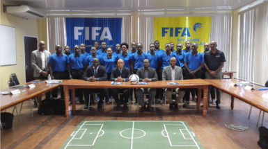 Peter Prendergast (2nd from left), FIFA Regional Development Officer/Technical Officer posing alongside GFF President Wayne Forde (2nd from right) and several of the participating referees following the conclusion of the RAP opening ceremony