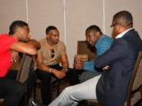 WICB president, Dave Cameron (right) chats with players Kieron Pollard (left) and Dwayne Bravo (second from left), and West Indies players union president, Wavell Hinds, during the symposiu