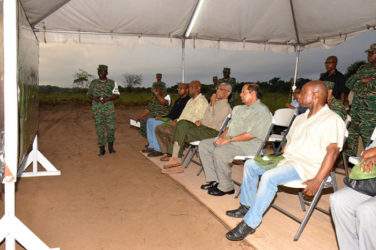 President David Granger (seated fourth from left) pays keen attention as Deputy Chief-of-Staff of the Guyana Defence Force Colonel George Lewis explains the elements of exercise 'Homeguard.' Minister of Foreign Affairs Carl Greenidge (seated at right), Prime Minister Moses Nagamootoo (seated second from right) and Minister of State Joseph Harmon (seated third from left) also look on. (Ministry of the Presidency photo)