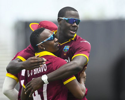 Carlos Brathwaite embraces Dwayne Bravo as they celebrate another Indian wicket during the opening Twenty20 International of the two-match series on Saturday. (Photo courtesy WICB Media)