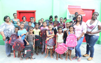 A group of children from Joshua House who received donations of backpacks and stationery from the Guyana Goldfields' Women in Mining Group. In photo are: Gladys Accra, Administrator of the Joshua House Orphanage (left), Maya Layne (second, left), Trudy Ferrier (third, left), Nichola Scott (right) and Marisa Hohenkirk (second, right) of the Women in Mining Group.