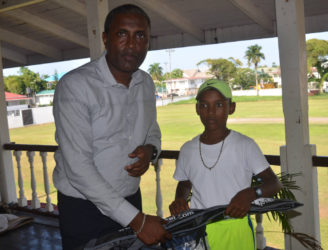 Best under-15 player Daniel Mootoo receives a pair ofpair of gloves from Club President AlfredMentore.
