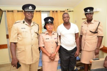 From left, Assistant Commissioner of Operations Christopher Griffith, Deputy Superintendent of Police and Welfare Officer of the GPF Loreine Saul and DSM Maxine Graham with Victor Faucette (second from right) in his hospital room. (GINA photo)