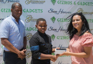 Pre-Cadet Caribbean U11 champion Kaysan Ninvalle (centre) receives the Samsung S7 Galaxy Edge phone from Gizmos and Gadgets Manager Sophia Dolphin while GTTA President Godfrey Munroe looks on.