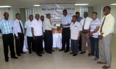 NBS CEO Mr. Anil Kishun hands over the sponsorship cheque to GCA President Roger Harper.