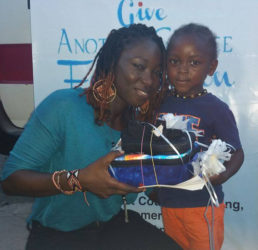"""Cultural Ambassador of Give Another Chance Foundation, Melissa """"Vanilla"""" Roberts handing over footwear and backpack to a child."""