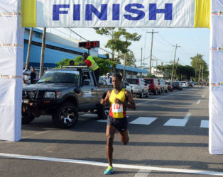 SIX IN A ROW! Cleveland Forde cruising across the finish line yesterday to win his sixth consecutive Massy 10k event. (Orlando Charles photo)