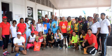 Country Manager of Massy, Deo Persaud and other employees take a photo opportunity with the top performers following the seventh annual 10km road race yesterday. (Orlando Charles photo)