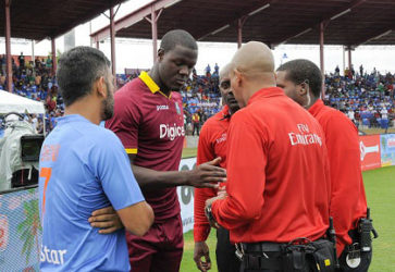 India captain MS Dhoni (left) discusses the abandoned T20 International with West Indies captain Carlos Brathwaite and match officials. (Photo courtesy WICB Media)