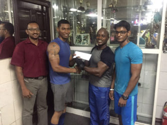 Senior trainer at Buddy's Gym, Mervyn 'Spongy' Moses recently presents a cheque to Dmitry Chan ahead of the Raw National Championships on September 18 at the Critchlow Labour College.