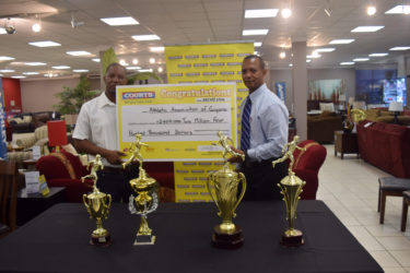 President of the AAG, Aubrey Hutson (right) receiving the sponsorship cheque yesterday from Courts (Unicomer Guyana Inc.) Marketing Managing Manager, Pernell Cummings.
