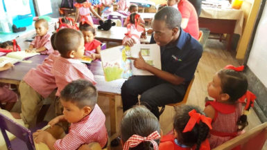 A Digicel employee reading to a group of students from the St. Cuthbert's Mission Nursery School as part of a World Literacy Day activity on Thursday. (Digicel Guyana photo)