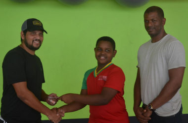 Proprietor of Fitness 53 and former West Indies batting ace Ramnaresh Sarwan (left) handing over the lifetime membership card to Kaysan Ninvalle (centre) while GTTA President Godfrey Munroe looks on