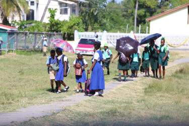Students of the Company Road Primary School (in blue in foreground) and the Buxton Primary School (in green in background) head home after the end of classes at the Company Road Primary where both schools are now being housed.