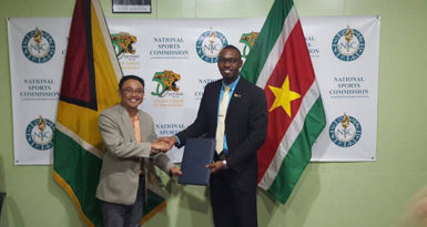 FLASHBACK! (L-R) Suriname Director of Sport, Luciano Mentowikromo and Guyana's Christopher Jones display the Inter-Guiana Games agreement.