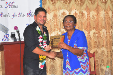 Ramnaresh Sarwan receives the plaque from his former Headmistress at Stella Maris `Primary School, Mrs Natalie Author.