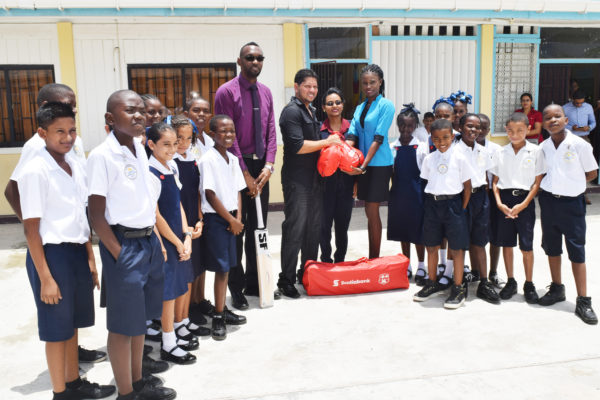 Stella Maris Primary School Headmistress Shivanie Singh receives some cricket gear from Ramnaresh Sarwan, in the presence of students and a teacher. NSC's Christopher Jones is to the left of Sarwan.
