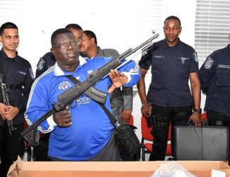 Police Sgt Matthew Haywood displays an assault rifle at the Maloney Police Station last week, one of eight firearms seized during a police exercise earlier this month. Looking on are the officers who took part in the exercise.