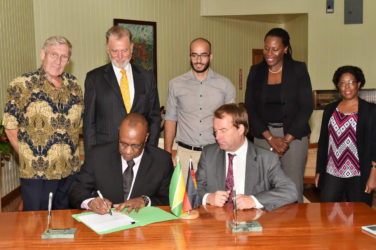 Minister of State Joseph Harmon signs the agreement as Germany's Regional Director for Latin America and the Caribbean Ambassador Dieter Lamle (seated at right) looks on at the Ministry of the Presidency yesterday. Also looking on are (from left) Honorary Consul of Germany to Guyana Ben ter Welle, Germany's Ambassador to Guyana Lutz Hermann Gorgens, Commissioner of the Protected Areas Commission (PAC) Damian Fernandes, Ms. Ndibi Schwiers-Ceres and Deputy Commissioner of the PAC Denise Fraser. (Ministry of the Presidency photo)