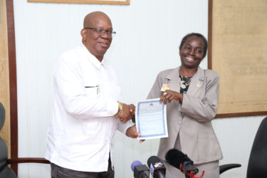 Minister of Finance Winston Jordan hands over one of 20 signed debenture certificates to General Manager of the National Insurance Scheme Doreen Nelson. (Photo by Keno George)