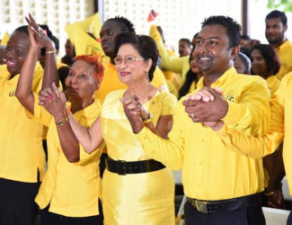 Opposition Leader Kamla Persad-Bissessar (second from right) holds hands with UNC Local Government candidates on Saturday at Couva South multipurpose hall during a song at the candidates' presentation.