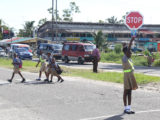 Road safety: St Pius Primary School's Road Safety Patrol pupils helping peers cross the street after school yesterday afternoon. (Photo by Keno George)