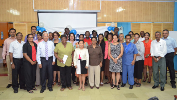 Country Manager Deo Persaud (third from left in front row) and senior managers pose with representatives of the 24 organisations. (Massy photo)