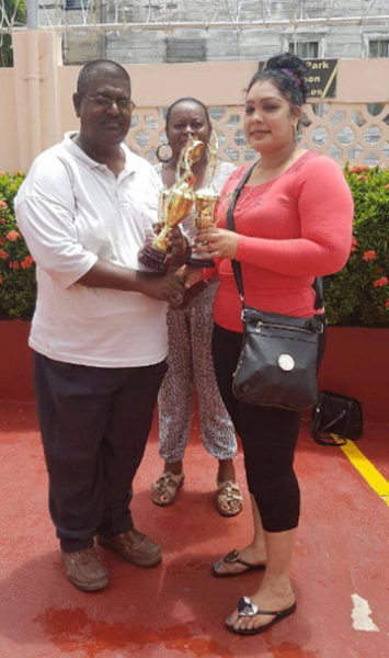 In picture president of the Guyana Draughts Association Jairam is seen receiving the trophies from a representative of the Berbice Bridge Inc., while the secretary of the GDA Marlyn Ali looks on.