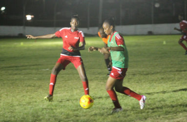 GDF's Odesa Romeo (right) trying to keep possession of the ball while being pursued by Tiandi Smith of Foxy Ladies during their matchup at the Camp Ayanganna ground